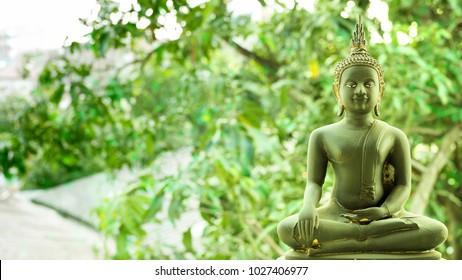 Buddha statue, seated and opened eyes buddha with tree bokeh