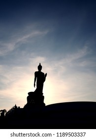 Buddha statue silhouette at Phutthamonthon is a buddha in the posture of walking.Important day in buddhism people walk around 3 times with lighted candle in hand. long shots background.