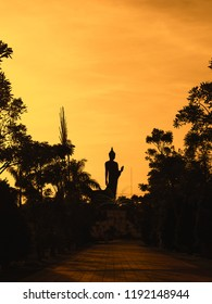 Buddha statue silhouette at Phutthamonthon is a buddha in the posture of walking.Important day in buddhism people walk around 3 times with lighted candle in hand.Medium shots  sunset background.