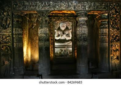 Buddha statue sitting inside Ajanta Cave with glowing walls in Maharashtra, India