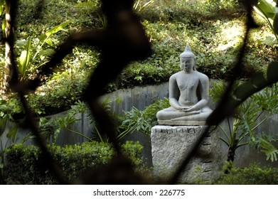 Buddha statue with smaller blurred statue in foreground.