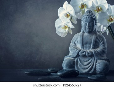 Buddha statue and stones on a black background