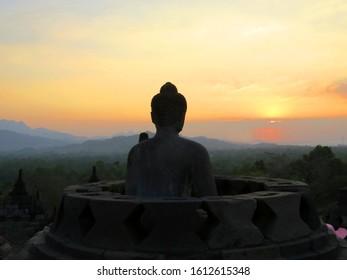 Buddha statue and stupa at the Borobudur in Java at sunset