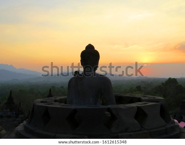 Buddha statue and stupa at the Borobudur in Java at sunset