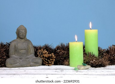 Buddha statue with tinsels, pinecones and two green candles on a wood table against a blue background