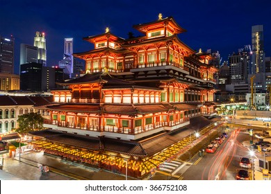 The Buddha Tooth Relic Temple comes alive at night in Singapore Chinatown, with the city skyline in the background. The temple is brightly lit in preparation for Chinese New Year.