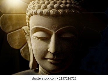 Buddha's head statue carved from sandstone by handmade artisan who believe strongly and faith in Buddhism with soft light background.