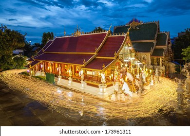 Buddhism light waving rite walk with lighted candles in hand around at Ming Muang Temple in Chiangrai , Thailand
