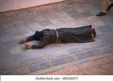 Buddhist aged pilgrim prostrates at the ground and prays during kora around Boudhanath stupa in Kathmandu, Nepal