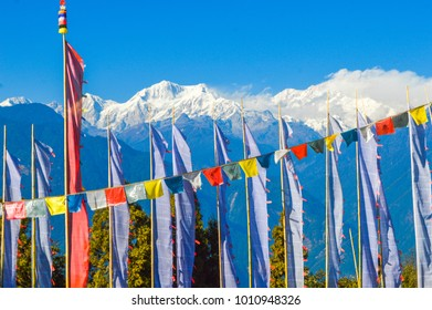 Buddhist banners against a Himalayan backdrop