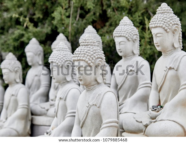 Buddhist Cement Statues in a row with shallow depth of field