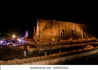 a Buddhist ceremony where people walk with lighted candles in hand around a temple