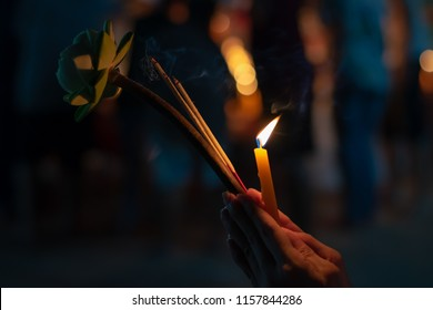 Buddhist ceremony where people walk with lotus, incense and candle in hand around temple at night,  Paying respect to Buddha with lighted