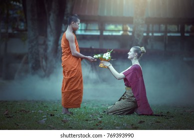Buddhist elder woman putting food offerings in a monk's alms bowl and a woman prostrating oneself to respect worship monks, monks walking routine every morning