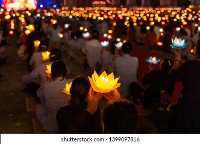 Buddhist hold lanterns and garlands praying at night on Vesak day for celebrating Buddha's birthday in Eastern culture