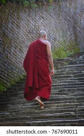 Buddhist monk climbing up stone stairs in Sri Lanka
