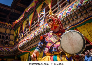 Buddhist Monk dancing and holding a drum at colourful mask dance at yearly buddhism Paro Tsechu festival in Bhutan monastery temple location.