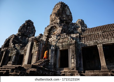 Buddhist monk dressed in orange climbing stairs entering a door at the facade of Bayon temple at the center of Angkor Thom complex in Siem Reap, Cambodia, South east Asia.