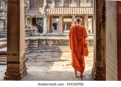 Buddhist monk exploring ancient courtyards of temple complex Angkor Wat in Siem Reap, Cambodia. Amazing Angkor Wat is a popular destination of tourists and pilgrims.