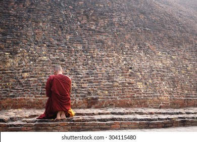 Buddhist monk kneeling to pray at the Buddha's cremation stupa in a foggy morning, Kushinagar, India