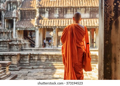 Buddhist monk looking at courtyard of ancient temple complex Angkor Wat in Siem Reap, Cambodia. Amazing Angkor Wat is a popular destination of tourists and pilgrims.