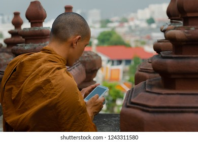 Buddhist monk looking at the smart phone on the top of the temple in Bangkok