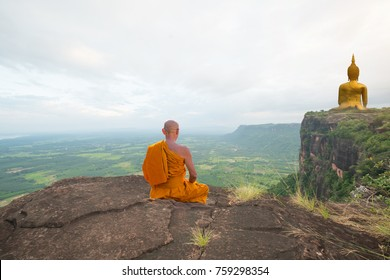 Buddhist monk in meditation at beautiful nature with golden buddha statue on high mountain