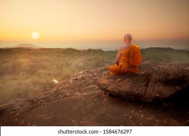 Buddhist monk in meditation at beautiful sunset or sunrise background on high mountain
