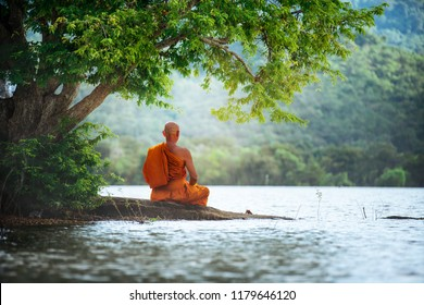 Buddhist monk in meditation beside the river with beautiful nature background