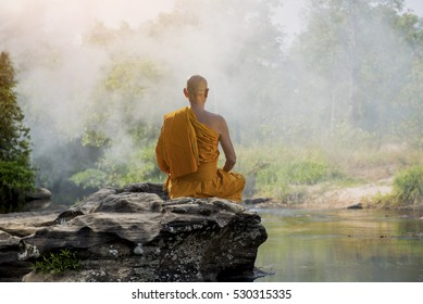 Buddhist monk in meditation in nature amidst the hot sun .