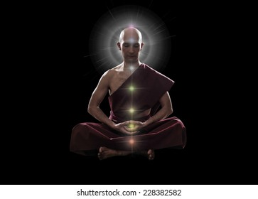 buddhist monk in meditation  pose with colorful Chakras over black background