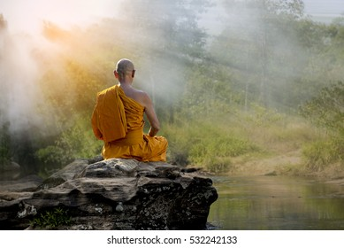 Buddhist monk in meditation at water fall in nature amidst the hot sun .