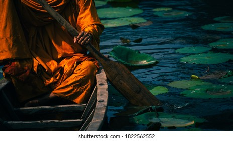 Buddhist monk in small boat sailing in canal, Thailand monk way of life.