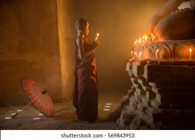 Buddhist monk, young novice monk myanmar lighting up candlelight inside a Buddhist temple, low light setting, Bagan, Myanmar.