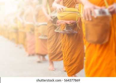 Buddhist Monks Line up in Row Waiting for Buddhism People to Give Alms Bowl in Thai Temple.  Blur Effect added to make Shallow Depth of Field.  Selective focus on Alms Bowl of Buddhist Monk.