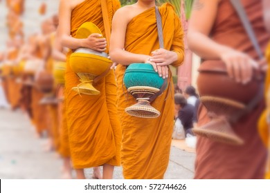Buddhist Monks Line up in Row Waiting for Buddhism People to Give Alms Bowl in Thai Temple.  Blur Effect added in this image.