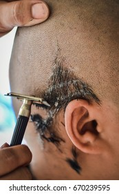 Buddhist monks shave their hair to be ordained a priest.Ceremony remove hair before to be monk.Hairdresser makes hairstyle bald man. The ritual culture of buddhism in Thailand.