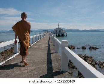 Buddhist monks stroll along the sea