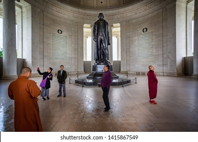 Buddhist monks studying statue of Thomas Jefferson in the Jefferson Memorial in Washington DC, USA on 13 May 2019