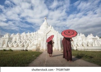 Buddhist monks with an  umbrella walking at the Hsinbyume Pagoda in Mingun
