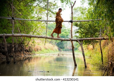 Buddhist monks walk across a wooden bridge