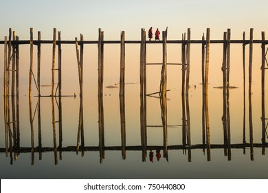 Buddhist monks walking on U Bein Bridge at sunrise in Amarapura, Mandalay, Myanmar (Burma).