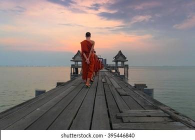 Buddhist monks are walking on a wooden bridge in the evening. Wood bridge beautiful sunset.Wood bridge beautiful twilight sunset.Bridge of Temple Djittabhawan.Long bridge extends into the sea.