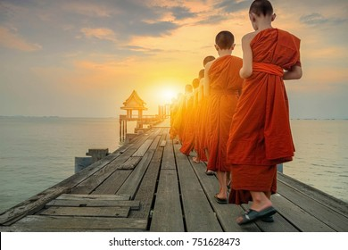 Buddhist monks are walking on a wooden bridge in the evening. Wood bridge beautiful sunset.Wood bridge beautiful twilight sunset.Bridge of Temple