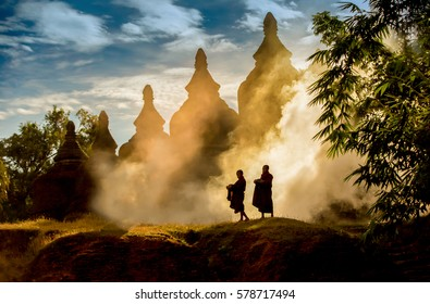 Buddhist novice monks walking outdoors pagoda background, children monk in Myanmar.