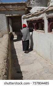 Buddhist nun turns prayer wheels at Lamayuru gompa monasteryLadakh, India