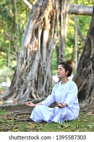Buddhist Nun woman or woman priest  or hindu nun smiling in white dress try to practice meditation and siting under the tree in the garden