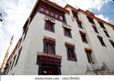 Buddhist old monastery with traditional tibetan decorations, wooden windows. Ladakh, Tibet region. White walls of big cultural object of buddhism
