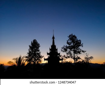 Buddhist pagoda silhouette with trees at sunset
