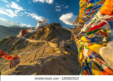 Buddhist Prayer flags connecting two peaks of Peak of Victory above Leh, India.  Monastery on the top of the hill.